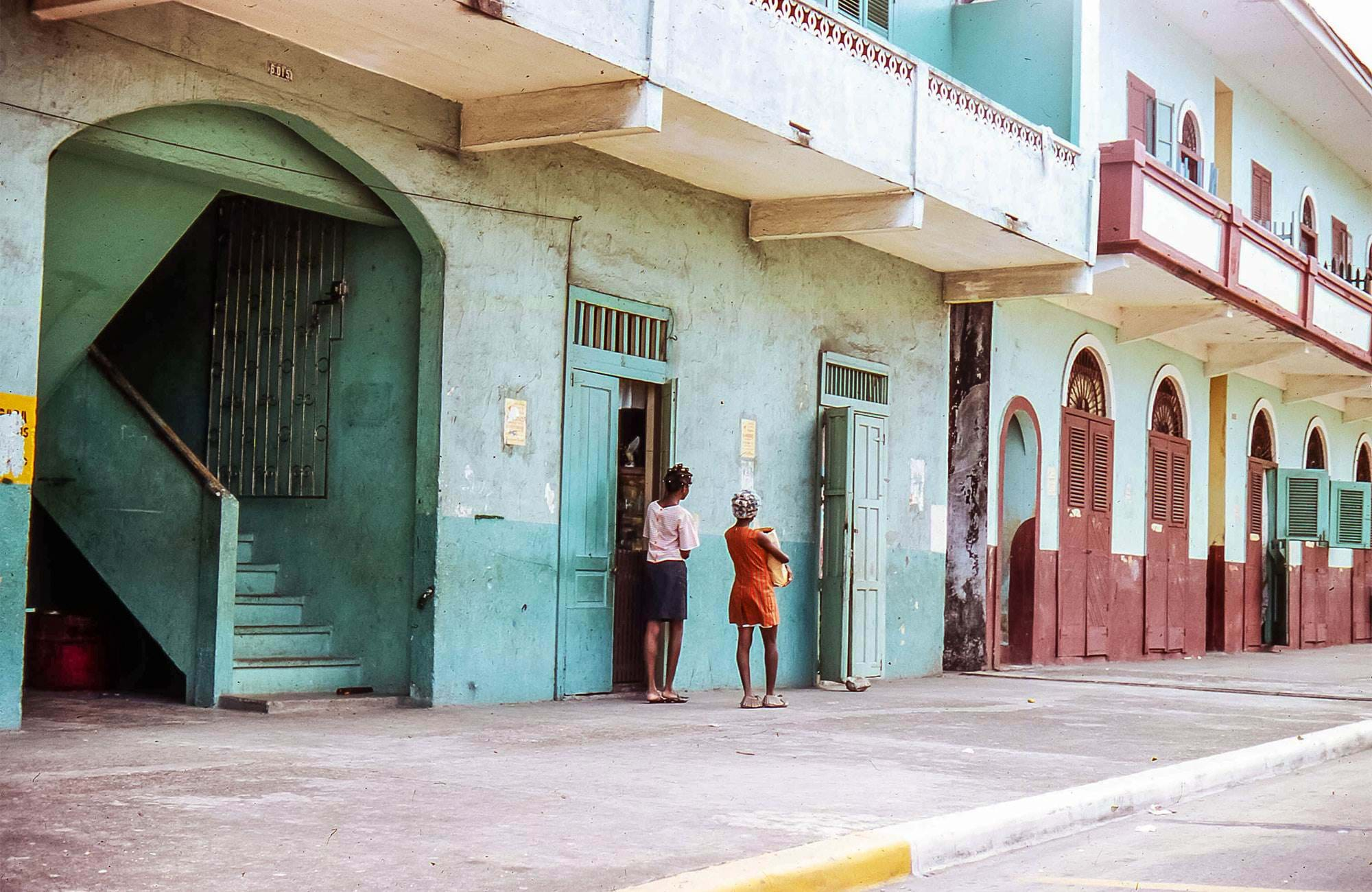 Street in Panama City with women standing in front of colourful colonial buildings