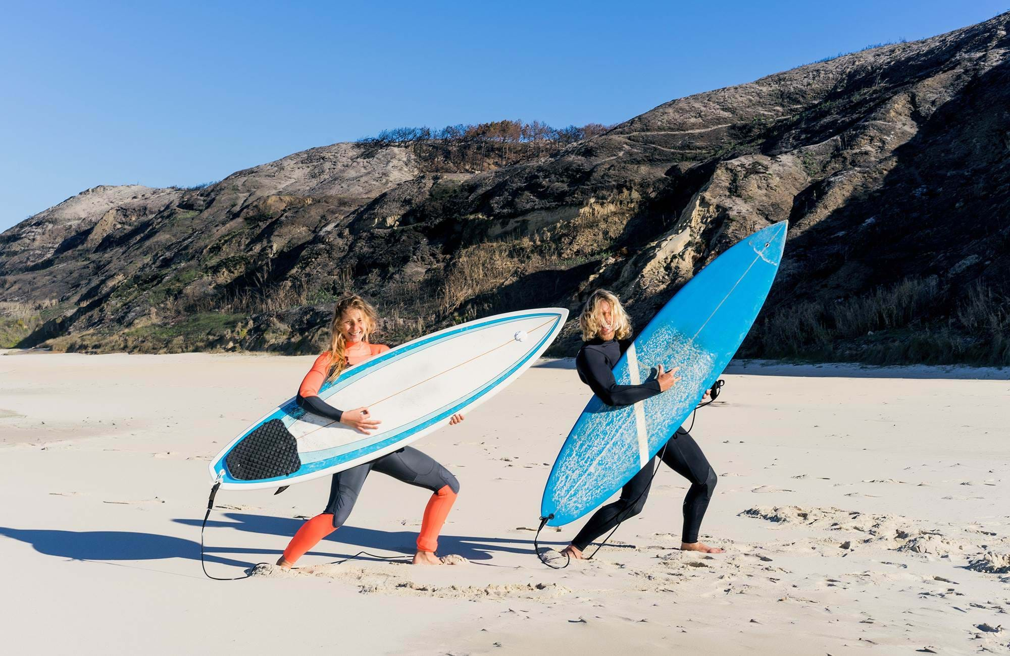 surfing-portugal-man-and-woman-playing-with-surfboards-on-beach-cover
