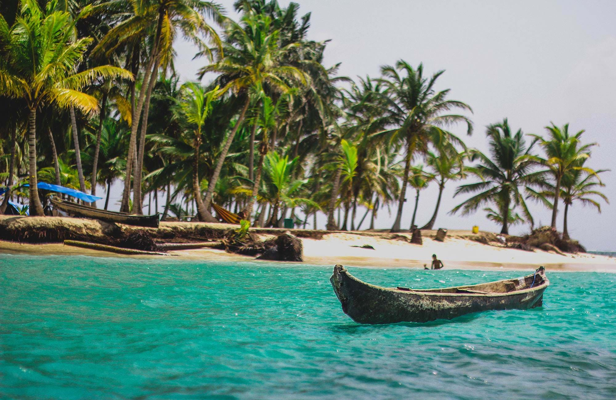 San Blas coast with palm trees and boats in clear turquoise waters, in Panama
