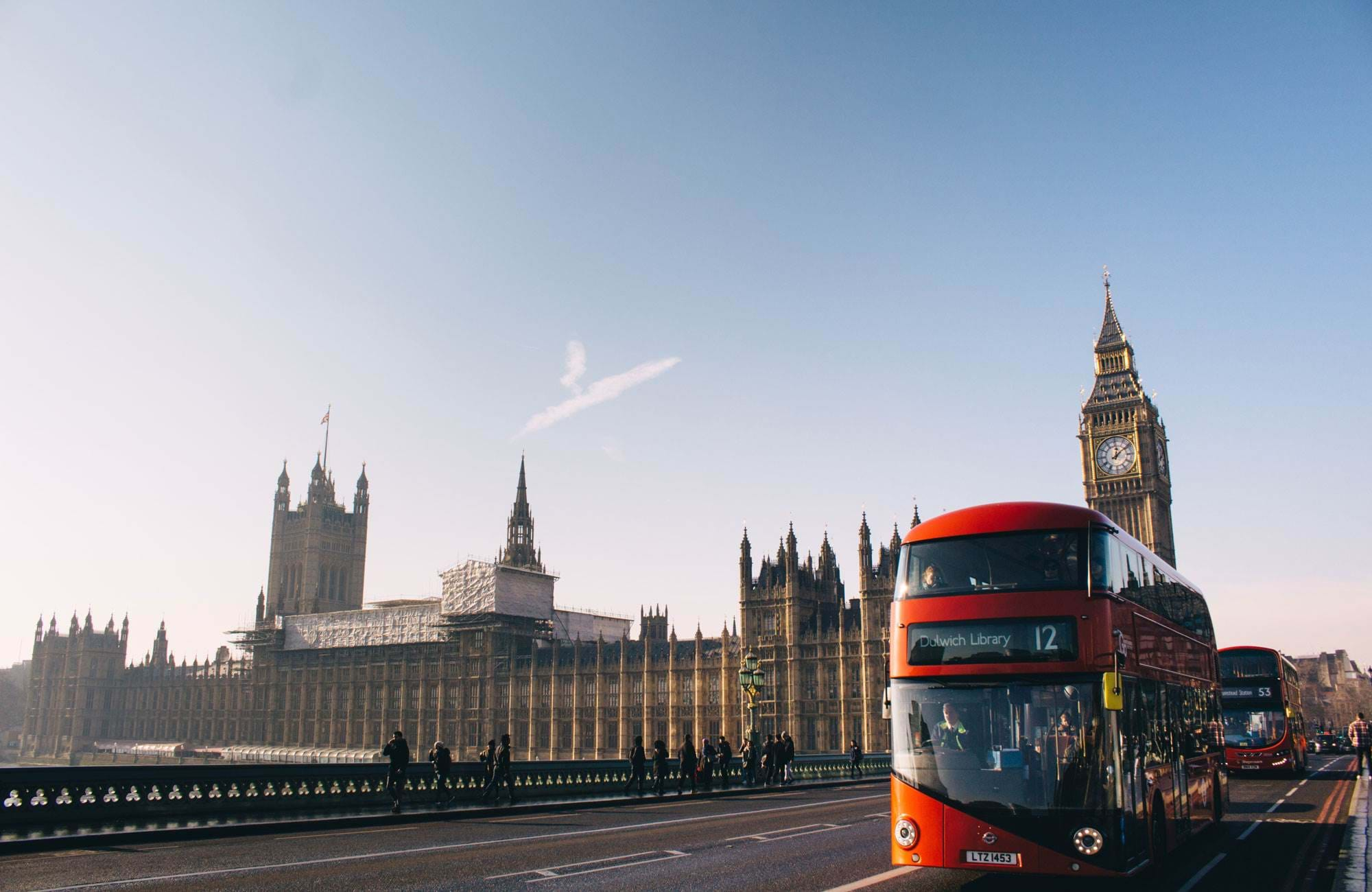 doubledecker bus in london driving past big ben on a sunny day