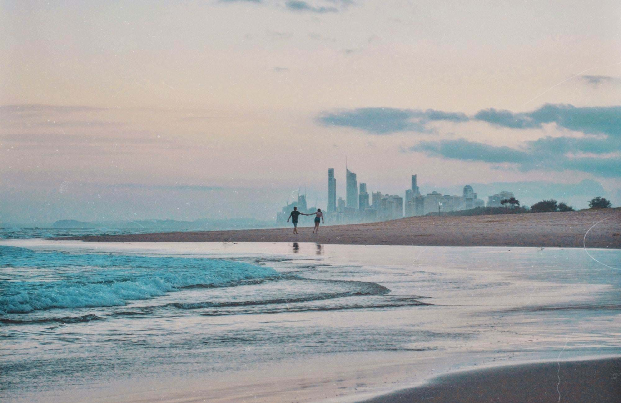 couple holding hands on australias gold coast and skyline
