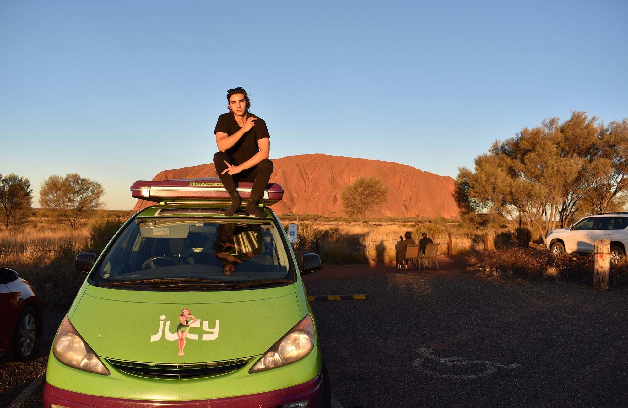 oliver on top of a jucy van in front of Uluru in Australia